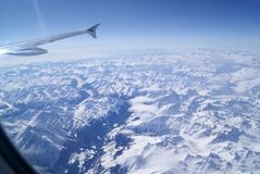 Vista de um avião sobre os cumes cobertos com a neve fotografia de stock