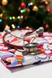 A vista de um estetoscópio vermelho que encontra-se no Natal esfrega com uma árvore de Natal no fundo foto de stock royalty free