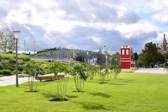 Vista de um gramado bem arrumado com arbustos lilás e de uma construção vermelha brilhante no parque de Zaryadye foto de stock