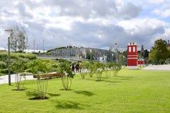 Vista de um gramado bem arrumado com arbustos lilás e de uma construção vermelha brilhante no parque de Zaryadye foto de stock royalty free