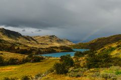 Vista de um lago e de um arco-íris no parque nacional de Torres del Paine em um dia nebuloso outono no Patagonia, chileno fotografia de stock royalty free