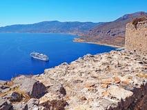 Vista de um navio de cruzeiros na baía da fortaleza da cume de Monemvasia, Grécia fotos de stock