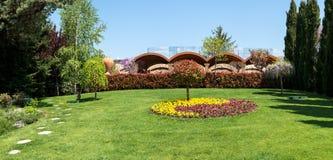 Vista de um quintal atrativo com flores de florescência, coníferas e gramados bem conservados imagem de stock royalty free