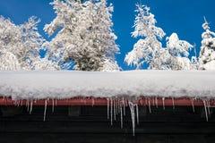 Vista de um telhado com nevadas fortes e sincelos foto de stock