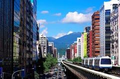 A vista de um trem que viaja nos trilhos elevados do sistema do metro de Taipei entre o escritório eleva-se sob o céu claro azul Foto de Stock Royalty Free