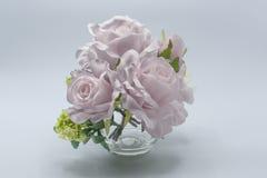 A vista de um vaso branco de vidro com as rosas de seda cor-de-rosa, com as várias folhas artificiais verdes, o fundo é misturada fotos de stock royalty free