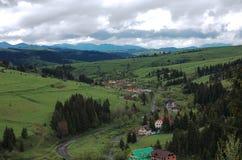 Vista de uma altura de uma estrada de enrolamento que passa através da vila Carpathian Fotos de Stock Royalty Free