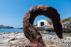 Vista de uma capela pequena pelo mar através de um gancho oxidado Foto de Stock