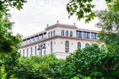 Vista de uma construção nova bonita, através do jardim de Ekaterininsky em quadrado Ostrovsky Imagens de Stock