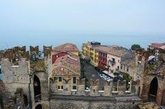 Vista de uma da torre velha do castelo dos telhados da cidade agradável Sirmione no lago Garda, Itália, dia nevoento, em novembro Imagens de Stock Royalty Free