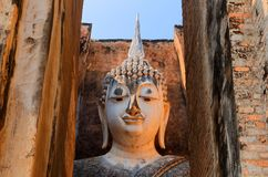 Vista de uma estátua antiga da Buda através da porta ao templo Wat Si Chum no parque histórico de Sukhothai Foto de Stock