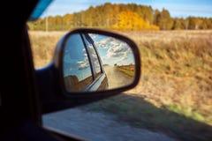 Vista de uma estrada secundária através do espelho de rearview fotos de stock royalty free