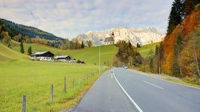 Vista de uma estrada secundária que passa por uma terra de exploração agrícola com uma igreja sobre o monte e a montanha Hochkoen Foto de Stock Royalty Free