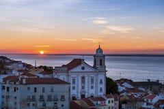 A vista de uma igreja na vizinhança de Alfama do Portas faz o ponto de vista do solenoide no nascer do sol em Lisboa, Portugal Imagens de Stock