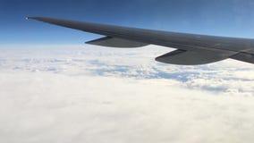 Vista de uma janela plana na asa e na paisagem abaixo dela Asa de um vôo do avião acima das nuvens filme