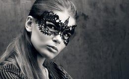 A vista de uma jovem mulher bonita na máscara preta do laço nos olhos Retrato preto e branco do close up foto de stock
