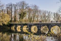 Vista de uma ponte com seus arcos que refletem no lago imagens de stock