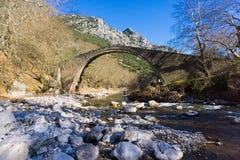 Vista de uma ponte de pedra onde os povos possam andar nela através de um trajeto paveled Imagens de Stock