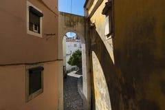 Vista de uma rua estreita com um arco e de construções velhas tradicionais na vizinhança histórica de Alfama em Lisboa, Portugal Fotos de Stock