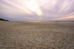 Vista de un canto ancho de la playa de la arena y de la disminución rosada Fotografía de archivo libre de regalías
