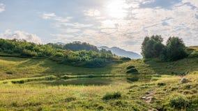 Vista de un lago de la montaña con agua lisa y de la reflexión, rodeada por la hierba y los arbustos, iluminados por el sol con imágenes de archivo libres de regalías