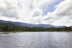 Vista de un paisaje de un lago rodeado por las montañas y los árboles Imagen de archivo