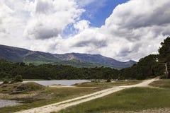 Vista de un paisaje de un lago rodeado por las montañas y los árboles Foto de archivo