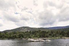 Vista de un paisaje de un lago rodeado por las montañas y los árboles Imágenes de archivo libres de regalías