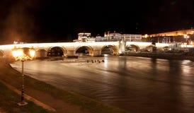 Vista de un puente y de un castillo de piedra famosos en Skopje, Macedonia, en la noche Fotos de archivo libres de regalías