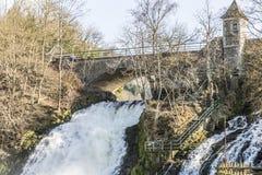 Vista de un puente y de una pequeña cascada en la pequeña ciudad del balneario Bélgica fotos de archivo libres de regalías