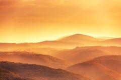 Vista de un valle en una madrugada hermosa con niebla entre h Foto de archivo