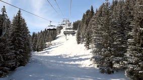 Vista de una cuesta alpina del invierno mientras que viaja en la telesilla a través de árboles metrajes