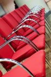 Vista de una fila vacante de sillas rojas imagen de archivo