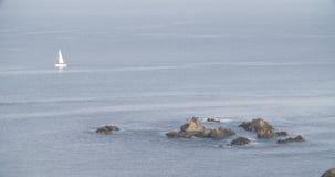 Vista de una formación de rocas en el mar con un velero en la esquina superior izquierdo almacen de video