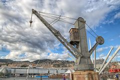 Vista de una grúa industrial vieja en el puerto antiguo de Génova, Italia, debajo de un cielo nublado fotos de archivo