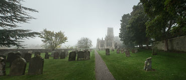 Vista de una iglesia a través de un cementerio en una mañana brumosa, Inglaterra Imagen de archivo libre de regalías