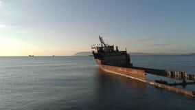 Vista de una nave oxidada de la ruina en un baj?o en el mar contra el cielo de la puesta del sol tiro Embarcaci?n mar?tima vieja almacen de metraje de vídeo