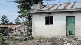 Vista de una pequeña casa en un pueblo pobre en África La basura miente alrededor del edificio destruido almacen de video
