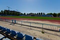 Vista de una pista corriente roja y de un estadio con un fie de la hierba verde Fotografía de archivo libre de regalías