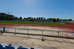Vista de una pista corriente roja y de un estadio con un fie de la hierba verde Foto de archivo