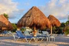 Vista de una playa arenosa tropical con los paraguas de la paja y los sillones rayados Imagen de archivo
