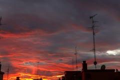 Vista de una puesta del sol imponente sobre una ciudad, rica en las nubes oscuras, rayos Imagen de archivo libre de regalías