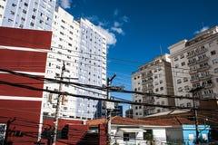 Vista degli edifici residenziali da una via commerciale con i cavi che passano vicino Fotografia Stock