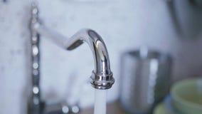 Vista degli inizio dell'acqua di rubinetto che entrano dal rubinetto nella cucina quando qualcuno lo ha acceso video d archivio