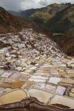 Vista degli stagni del sale, di Maras, del Perù, del Sudamerica con le Ande e del cielo nuvoloso Fotografie Stock Libere da Diritti