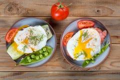 vista degli uova affogate con i pomodori e delle pipi su fondo di legno immagini stock libere da diritti