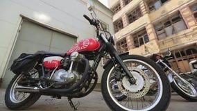 Vista dei motocicli con i dettagli rossi Sera di estate bikers Costruzione abbandonata motocicletta stock footage