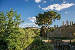 Vista dei mura di cinta e delle torri con gli alberi al tramonto a San Gimignano Immagini Stock Libere da Diritti