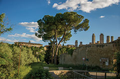 Vista dei mura di cinta e delle torri con gli alberi al tramonto a San Gimignano Immagini Stock