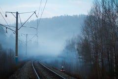 Vista dei pali ferroviari ed elettrici in nebbia in primavera fotografia stock libera da diritti